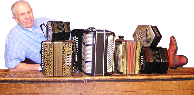Photo of John Kirkpatrick with accordions on a stage